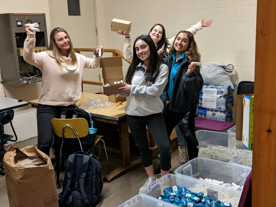 SGA members assemble care packages for service members using donated supplies.