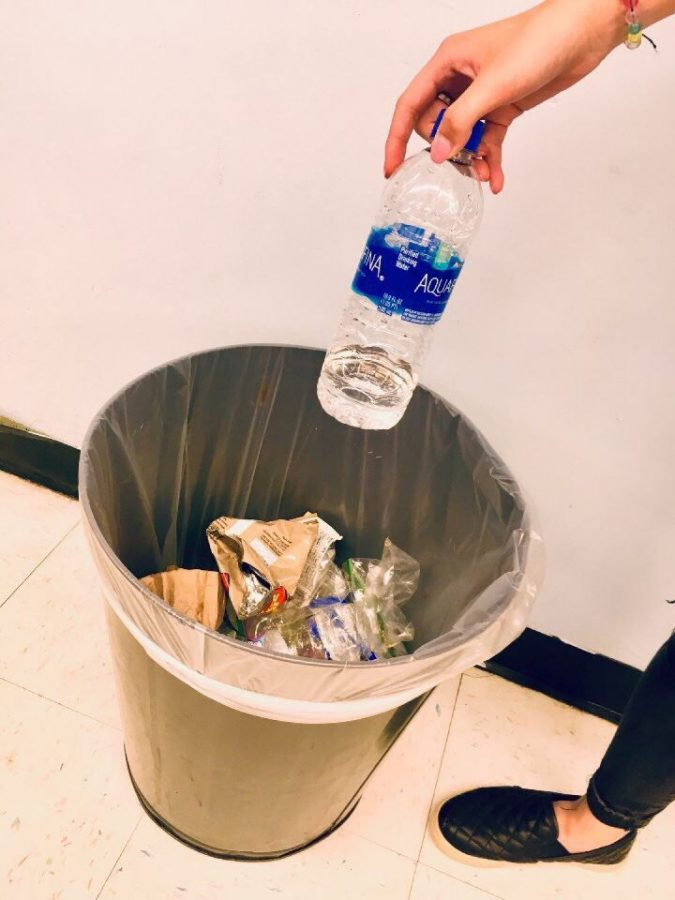 Student throws away recyclables.
