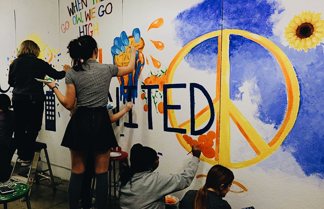 Syracuse students painting a mural over the graffiti.