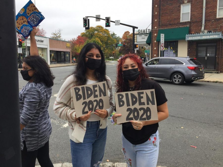 High school students Shreya Jyotishi (on the left) and Melissa DiDario (on the right) hold signs in support of Biden.
