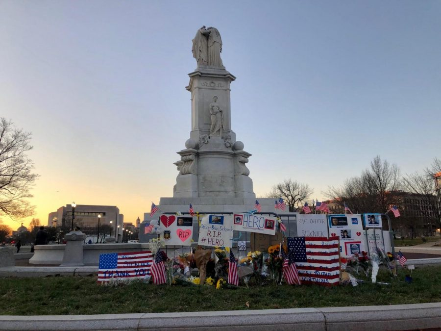Posters+adorn+the+Peace+Monument+on+the+grounds+of+the+Capitol+after+the+attack+on+Jan.+6